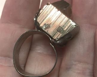 """ITEM 85: Metal Chunk Ring $22   Open, flexible size sterling band, supports chunk of an unknown metal """"crystal."""" Metal chunk is dark silver tone, but reflects some gold-tones under certain lights."""