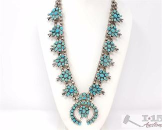 """222: TURQUOISE PETIT POINT SQUASH BLOSSOM NECKLACE. Value $2500.00 Vintage 1970's Navajo Sterling Silver Petit Point Turquoise and Sterling Silver Squash Blossom Necklace.  Big substantial piece, 174g. This beautiful mixture of green and blue turquoise is possibly from the Morenci mine.  Necklace is 13"""" down each side, not including the Naja.  Naja is 2.5"""" by 3"""".  6 Blossoms down each side, totaling 12 blossoms.  Each measuring 1"""" by 1.5"""". Beads are 1/4"""" , Necklace is strung on twisted silver rope."""