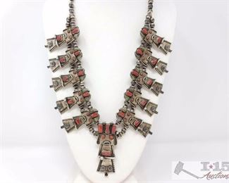 """224 NAVAJO CORN MAIDEN KACHINA SQUASH BLOSSOM NECKLACE. Value $4500.00 THIS NECKLACE IS AN INCREDIBLE AESTHETIC TOUR DE FORCE AND IS DESTINED TO BECOME AN HEIRLOOM. IT WAS HANDCRAFTED BY THE NAVAJO SILVERSMITH LAPIDARIST, FRANK YAZZIE. FRANK YAZZIE WAS FAMOUS FOR THESE INTRICATELY WORKED THREE DIMENSIONAL FIGURAL NECKLACES WHICH HAVE BECOME RATHER RARE AND ARE THEREFORE HIGHLY SOUGHT AFTER SINCE HIS DEATH. THE NECKLACE IS ARRANGED LIKE A TRADITIONAL NAVAJO SQUASH BLOSSOM WITH 5 MATCHING KACHINA PENDANTS ON EITHER SIDE OF A OF A LARGER KACHINA WHICH FUNCTIONS AS A NAJA. THE 10 SMALLER KACHINAS FUNCTION AS THE """"BLOSSOMS"""" THE MIDDLE KACHINA IS HALLMARKED """"FY"""" AND """"STERLING"""". IT IS ABOUT 3 INCHES IN HEIGHT BY 1-1/8 INCHES IN WIDTH. IT HAS 6 NATURAL RED CORAL STONES SET IN SERRATED BEZELS MAKING UP THE EYES,HEADDRESS AND UPPER GARMENT. THE HEADDRESS HAS DECORATIVE SILVER RAINDROPS. THE SKIRT OR LOWER GARMENT HAS TRADITIONAL STAMP WORK. IT IS FRAMED BY TWISTED WIRE WORK AND FRAMED BY TWISTED"""