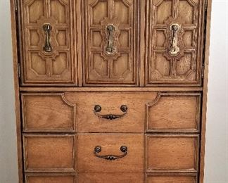 Tall chest of drawers that open on top to reveal more drawers and storage.