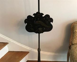 "19th Century wood fireplace screen.  Black with gilded accents and a painted peacock on the screen itself.  The screen can be moved up and down.  It is 54"" high and the screen, at the widest point is 15"" across.  Price: $55.00"