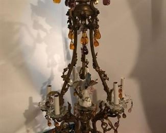 "Louis XV style gilt bronze and porcelain mounted chandelier.  Of birdcage form, with six scrolling foliate candle arms hung with colored and clear glass fruit, the center mounted with a porcelain parrot.  This piece is approximately 42"" high and 18"" at its widest point.  Price: $1800.00"