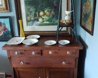"""antique dresser with replacement knobs. tea leaf ironstone dishes. small """"bamboo"""" 4 leg table with amber compote on top. cambridge creamer and sugar (amber). fruit prints in old frames."""