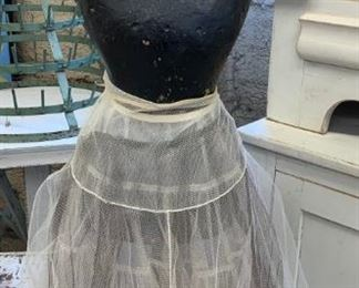 Vintage Paper Mache mannequin from France on rolling heavy iron base. We do not see any markings as the mannequin has been painted and leaves an aged black tonne. There are three vintage petticoats layered on the mannequin that come with it. $325
