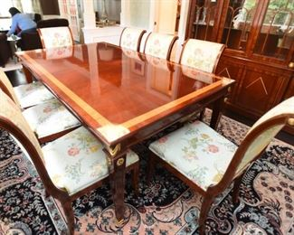 """ITEM 1: Kindel Neoclassical Rectangular Dining Table  $995:  This table is based on popular turn-of-the-century desk forms which featured fluted legs and swags. The center field of this Neoclassic style table is figured Mahogany and features a cross-banded border of Mahogany and Satinwood. The border is separated on both sides with inlays of black, Maple, and Tulipwood. The fluted legs are topped off by solid brass rosettes. The swag carvings and feet are gilt leaf . There are three 16"""" leaves with aprons. 78"""" long (no leaves) x 46"""" wide x 30.25"""" high. Fully extended 126"""". Table top is in very good condition. There are some scuff marks that should polish out, but no deep scratches, blemishes or sun fading. Pads included."""