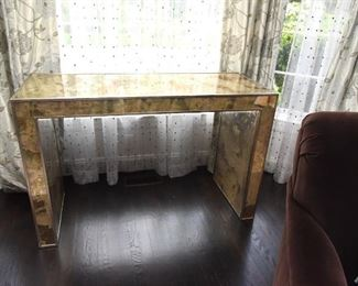 """ITEM 16: Mirrored Sofa Table  $325 Mirror finished with swaths of gold, copper, bronze tones. 50.5"""" wide, 20"""" deep, 32.5"""" tall"""