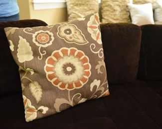 """ITEM 72: Three Orange Flower Pillows  $30 Each pillow is brown with orange, cream, and tan flowers. 19.5"""" square."""