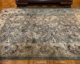 Dark green and earth toned area rug.