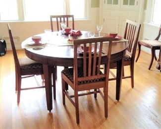 "1940s Craftsman Dining Table and 6 chairs, full table pads.  Solid wood, some wear marks.  Table measures 54"" without leaves, 5 leaves 9"" each, 99"" maximum length.  Includes 6  chairs 38h 18d 18.5w 18 seat height .  There are 4 other chairs with same seat covers, sold separately."