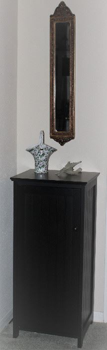 """Black Stove-Pipe Cabinet (36""""H x 16""""W x 14""""D) with 2 Adjustable Interior Shelves shown vintage Home Interior Decorative Wall Mirror (4"""" x 24"""").  Aim Bros Formalities Porcelain Basket and Satin Glass Lily Sculpture"""