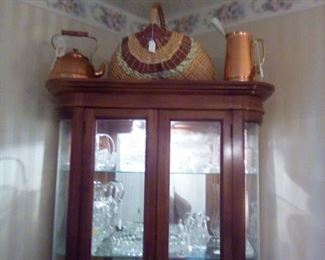 curio with copper tea kettle, pitcher and basket on top