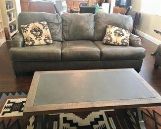 "Sleeper sofa, coffee table and machine made 5' 5"" x 7' 7"" rug."