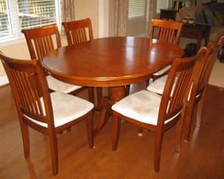Kitchen table with 6 chairs.  Leaf folds and stores in table top.
