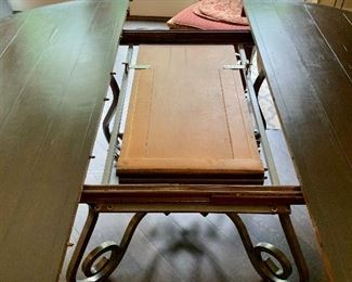 Detail: French country wrought iron base, wooden topped table with self storing collapsible leaf