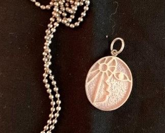 $110 Guayasamin for Taller (Mexico) Modernist sterling silver pendant and silver tone beaded chain.  Oval pendant has a face looking at the sun in relief.  Reverse signed
