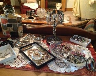 Entertainment center topped with table runner,  doilies, decorative bottle and lots of Jewlery.