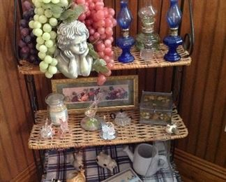 Metal and rattan shelving unit, mini oil lamps, angel bowl with grapes, small fruit print-framed
