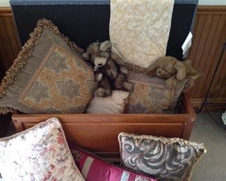 Chest full of decorative pillows and mink look teddy bear and dog