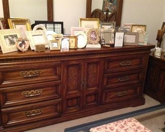 Large dresser with double mirrors and collection of picture frames