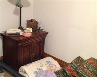 One of a pair of nightstands, lamp, vintage phone/clock/ radio, decorative box, candleholder, candle, bedspreads