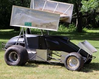 Lot 4 : 1990s Schnee sprint car. Rolling chassis and rear end with Wildwood disc brake, aluminum radiator, rear fuel cell, full roll cage,  top and front wing and Kirkey seat. Includes fair Hoosier racing tires, left side tires do not hold air.