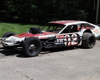 Lot 2: 1980s modified open wheel race car, custom built by Ambro Race Cars, Ascutney Vt. With Precision Powered small block Chevy V-8 engine, 4BBL Holley carburetor, 4-wheel Wildwood disc brakes, jaz fuel cell and Hoosier racing tires. Starts and runs well. Includes 4 extra tires and wheels in fair condition.
