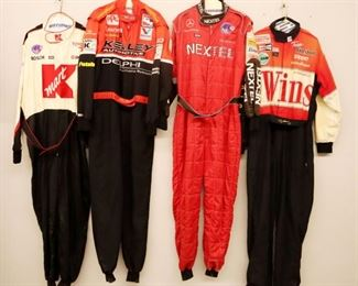 Lot 9: Four Simpson racing suits. All one piece suits and race worn with various sponsor logos. General wear and fading. Size Large and Extra Large.