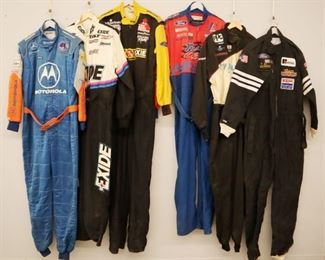 Lot 10: Six racing suits. All one piece suits and race worn with various sponsor logos. General wear and fading. Size Large and Extra Large.