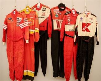 Lot 11: Six racing suits. All one piece suits and race worn with various sponsor logos. General wear and fading. Size Large and Extra Large. ESTIMATE $100-200