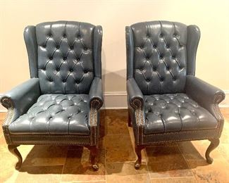 pair of navy blue leather wing back chairs
