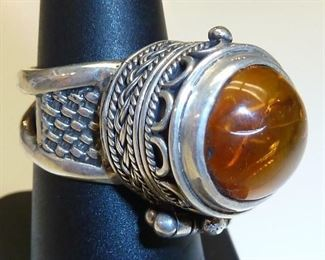 Yes yes yes!  Amber poison ring set in Sterling silver.  It is adjustable too.  More pictures available.  $245