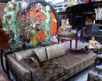 One of two sofas with silk upholstery. Thai dancers and floral arrangements lend a theatrical air to the space. Lamp with gold figure and black shade is one of three pairs still available.
