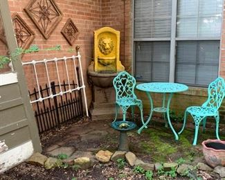 Front Entrance:  More outdoor decorations.  An old door, headboard, metal and wood wall art, garden gates, Lion head fountain, three piece table set, bird bath, flower pot.  Not pictured, old wooden school desk, broken tile mosaic decorated top flower stand, birdfeeder on a pole, shepherds hook.
