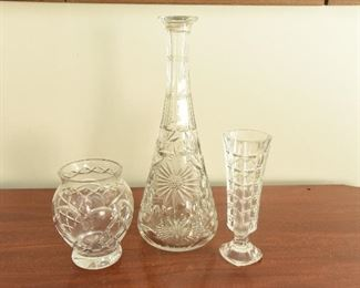 """4. Three Crystal Items  $22 Small vase, marked Roguska  5"""" tall, 4.5"""" wide Cut crystal decanter; no stopper. Unmarked. 12.25"""" tall, 5"""" base. Fleabite chips and scratches on the bottom. Umarked bud vase. 6.625"""" tall, 2"""" base. Some fleabite chips."""