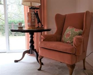 Wing back armchair and a mahogany tilt-top round table