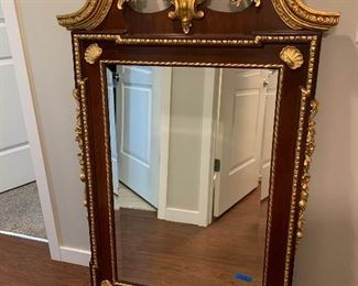 "Lot 498. $1500. Shell Gold Leaf Looking Glass. From The Sutton Collection by Century. (Retails for $3000). This design is a classic late 18th Century looking glass. It is distinguished by its pierced and inlaid shell medallion at the top center, flanked by scrolled leaves and side garlands of acorns, leaves, and flowers. This mirror design can be dated after 1770 by the characteristic treatment of the fillet, undulated at the top corner but squared at the bottom. The ornamentation on the striped mahogany fretwork panel is all hand-laid antique gold leaf and highlighted by beveled glass. Mirror measures 22.5"" x 47"""