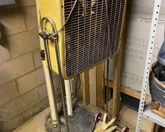 Vintage mustard yellow fan with metal blades and portable stand.