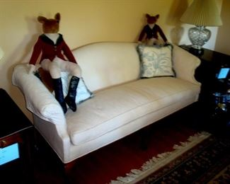 Chippendale style sofa in white upholstery with down cushion and decorator stuffed animals.