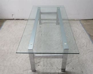 """ITEM 65---MCM chrome base, glass top coffe table. [small chip glass at corner]. 54"""" long, 25"""" wide, 16' high $225.00"""