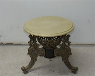 """ITEM 68---Classical style figural gilt metal, composition marble top pedestal with cherubs. 18"""" high, 18"""" diameter, 24' base width at feet. $100.00"""