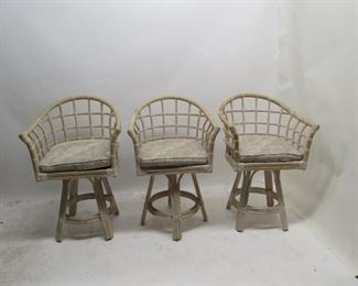 """ITEM 99---3 rattan swivel bar stools w cushions, 1 w/ rips and stains, 24 3/4w, 19"""" deep, 38.5"""" high, 22.5"""" high to seat.              $ 150.00"""