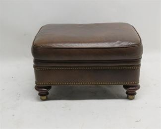 ITEM 105---leather ottoman with wood and brass feet, brass tacking.  some surface wear, $75.00