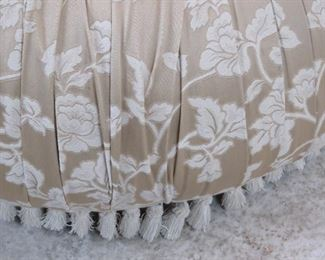 upholstered pleated ottoman on legs, missing a couple tassels.  PIC 2