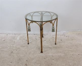 """Item 287-- Hollywood Regency iron and glass top table with tassel and leaf design. [paint discoloration]. 22"""" diameter, 22"""" high $175.00"""