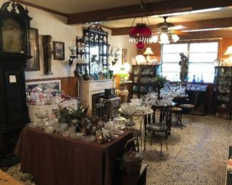 The Ice Cream Parlor with EAPG Early American Pressed Glass, another beautiful antique grandfather clock, mirrored display shelf, ruby red oil lamp chandelier, Gone with the Wind electrified oil lamps, ice cream parlor metal chairs and tables.