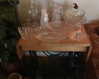 Vintage sewing machine stand, repurposed as table, with beautiful pressed glass
