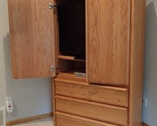 OAK ARMOIRE WITH DRAWER STORAGE AND TV OR STORAGE BEHIND DOORS.