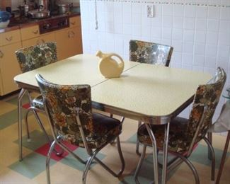 Kitchen:  A 1950's kitchen set has a yellow/black top (a closer photo follows) and four floral chairs.  There is a self-storing leaf inside the table.