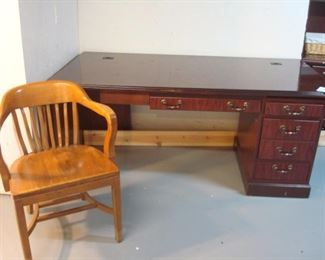 Lower Level:  A vintage office chair is n front of a cherry desk.