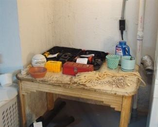 Lower Level:  A vintage wood kitchen table displays two drills (one DeWalt and one Black & Decker in cases) as well as sets of DeWalt drill bits and various household goods.